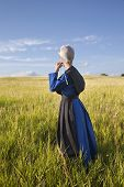 Amish Woman Standing In Grassy Field With Afternoon Sunlight