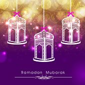 Hanging intricate arabic lanterns on shiny abstract background for celebrations of holy month of Ram