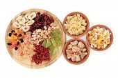 Dried fruit selection on a wooden board and in terracotta bowls over white background.