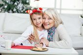 Portrait of loving grandmother and girl with cardpaper smiling during Christmas at home
