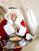 Man in Santa costume with cookies and milk sleeping in private jet
