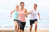 Group running on beach jogging having fun training. Exercising runners training outdoors living healthy active lifestyle. Multiracial fitness runner people working out together outside smiling happy.