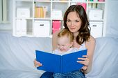 Beautiful young mother with her little baby at home reading a book.