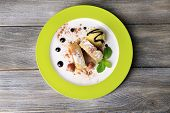 Tasty homemade apple strudel with nuts, mint leaves and ice-cream on plate, on wooden background