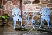 Blue painted metal outdoor furniture on stone patio