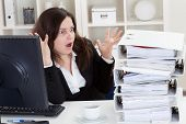 Businesswoman Shocked By Watching Stack Of Folders