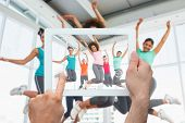 Hand holding tablet pc showing fitness class and instructor jumping in fitness studio