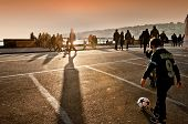 children playing football at sunset in Naples, Italy