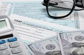 stock photo of cpa  - Tax Form 1040 with calculator dollars and glasses - JPG