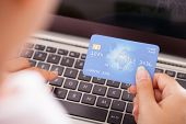 Female Holding Credit Card Over Keyboard