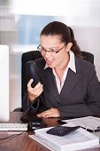 Angry Businesswoman Shouting On Telephone In Office