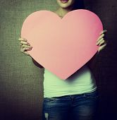 stock photo of incognito  - portrait of young woman holding pink heart incognito - JPG