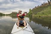image of horsetooth reservoir  - senior athletic paddler in a  decked expedition canoe photographing on a lake with green vegetation  - JPG