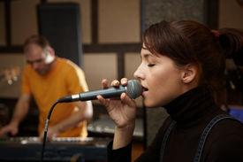 image of recording studio  - vocalist girl is singing in studio - JPG