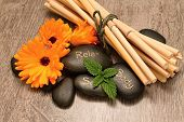 pic of bamboo leaves  - Black lava stones and flower marigold blooms on wooden boards with melissa leafs and bamboo in background placed on wooden board - JPG