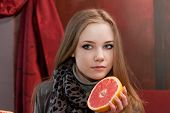 Young girl with half a grapefruit in hands on a background of interior cafe