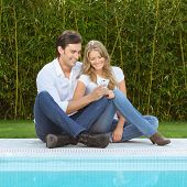 Couple sitting on the grass by the pool checking the smart phone