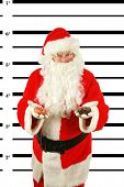 BUSTED. Santa Claus is arrested and his MUG SHOT taken at the Police Station. Santa was a Bad Bad boy.  He even tried to Bribe his Freedom from the Police with Donuts knowing they are hard to resist.