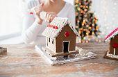 cooking, people, christmas and decoration concept - close up of happy woman making gingerbread houses at home