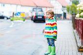 Happy Cute Little Boy Walking In City Through Rain