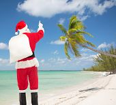 christmas, holidays, travel and people concept - man in costume of santa claus with bag pointing finger from back over tropical beach background
