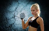 sport, fitness, training, weightlifting and people concept - young sporty woman with dumbbell flexing biceps over concrete wall background