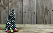 Christmas tree with snow and presents by antique rustic wooden background
