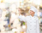 cooking, advertisement and people concept - smiling female chef, cook or baker pointing finger up to something over holidays lights background