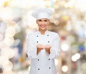 cooking, advertisement and people concept - smiling female chef, cook or baker holding something on palms of hands over holidays lights background