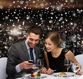 technology, food, christmas, holidays and people concept - smiling couple with smartphone eating at restaurant over snowy night city background