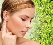 beauty, people and ecology concept - beautiful young woman touching or pointing finger to ear over green background