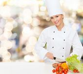 cooking, holidays, people and food concept - smiling female chef chopping vegetables over lights background