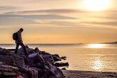 Traveller walking on rock cliff against sea, sunrise or sunset