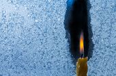 Closeup Of Little Candle Flame Behind Frozen Window Glass