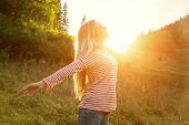 Happiness woman stay outdoor under sunlight of sunset