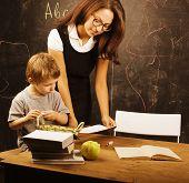 little cute boy with teacher in classroom at blackboard