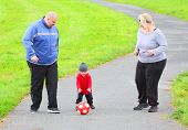 stock photo of child obesity  - Overweight parents with her son playing soccer together - JPG
