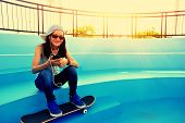 woman skateboarder sit on skatepark stairs listening music from smart phone mp3 player