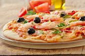 Pizza with shrimp, salmon and olives