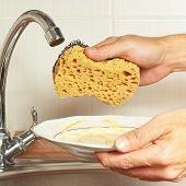 Hands with sponge and dirty dishes over the sink in kitchen