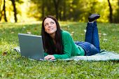 Woman using laptop and thinking