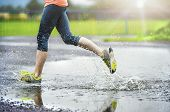picture of leggings  - Young woman running on asphalt sports field in rainy weather - JPG