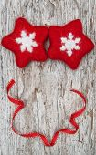 Two Red Woolen Snowflake And Ribbon On The Old Wood