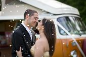image of campervan  - Happy just married couple in an orange classic camper van parked outside in a green field ready for camping and a piknick - JPG