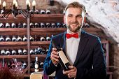 pic of wine cellar  - Sommelier with wine bottle in the wine cellar - JPG