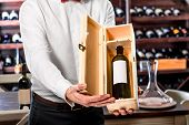 pic of wine cellar  - Sommelier showing wooden wine box with expensive wine in the wine cellar - JPG