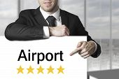 Businessman Pointing On Sign Airport