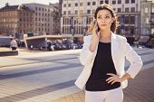 Beautiful Brunette Business Woman In White Suit Talking On A Cell Phone In Her Hands Outdoors. Copy