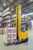 Driver Of Yellow Forklift Truck Operates, In Warehouses.