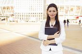 Beautiful Brunette Business Woman In White Suit With Folder Of Documents In Her Hands Outdoors. Copy